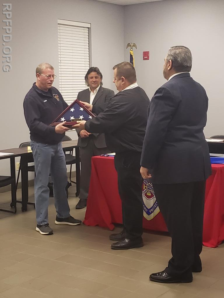 Fire Chief Ketchen presents Trustee Lorenz with a ceremonial flag in honor of his 16 years of service with the Board of Trustees.