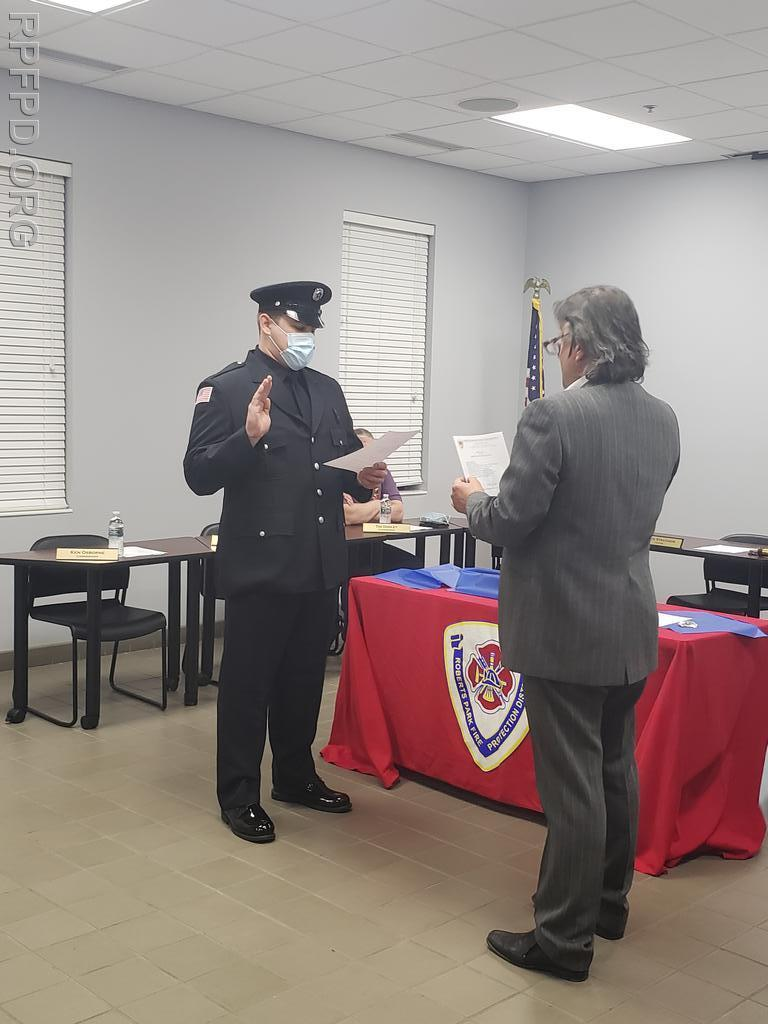 Trustee Steve Stratakos gives the oath of office to Nicholas Hooten during the swearing in ceremony on March 9, 2021.