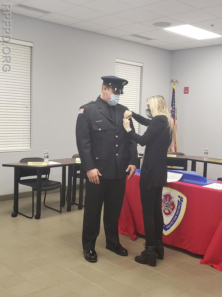 FF/PM Hooten's fiancé, Nicole, pins on his badge during the ceremony on March 9, 2021.