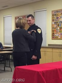 FF/PM Anthony Palkovitz's mother, Susan Elliott pins the ceremonial badge on her son.