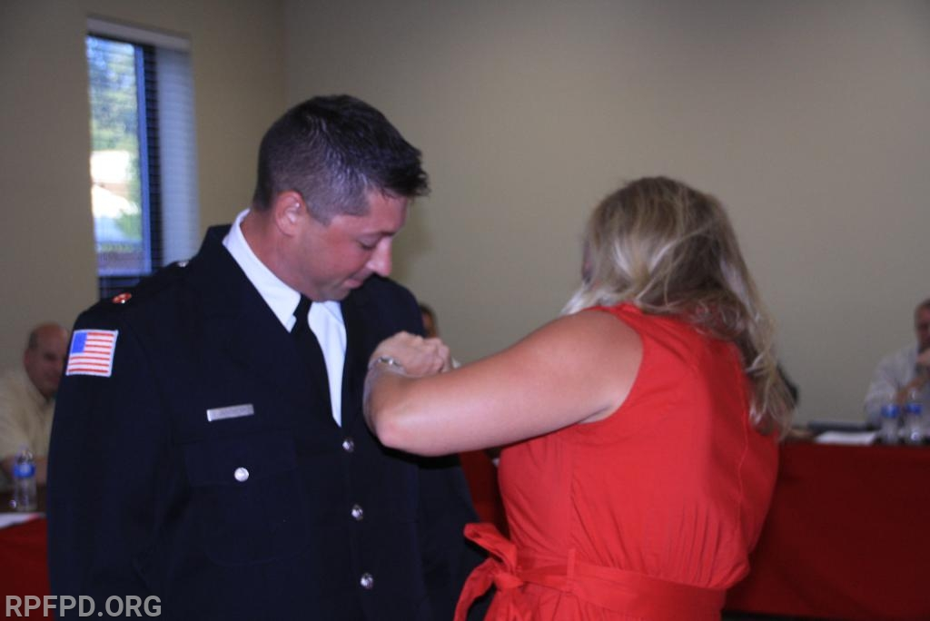 James has his badge pinned on by his wife, Maripat, as he is joined by his family and friends.