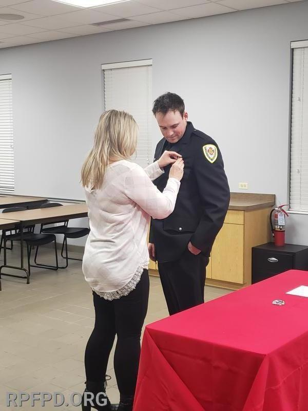 FF/PM James Evans' mother, Rhonda, pins his badge on during the swearing-In ceremony. 12/10/2019