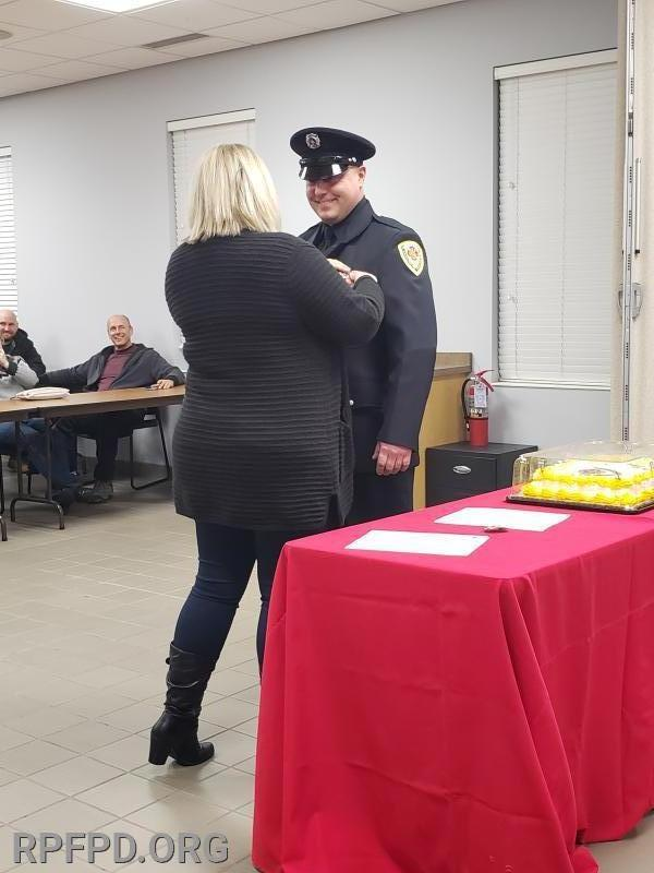 FF/PM Dan Bikulcius' wife, Christin, pins his badge on during the swearing-In ceremony. 1/14/2020
